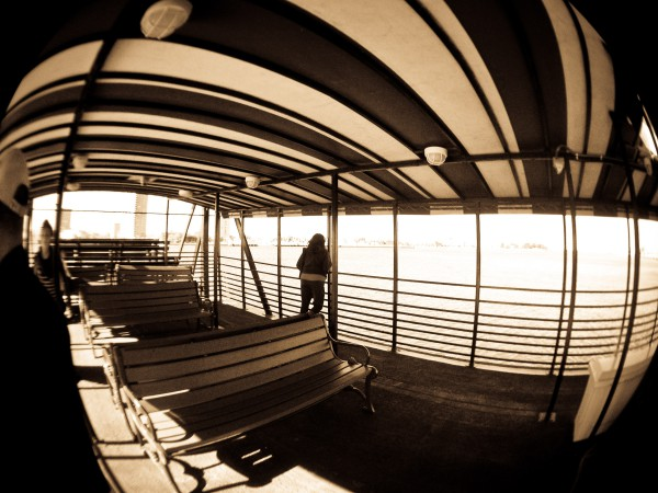 Sepia photo of a lone person on a ferry