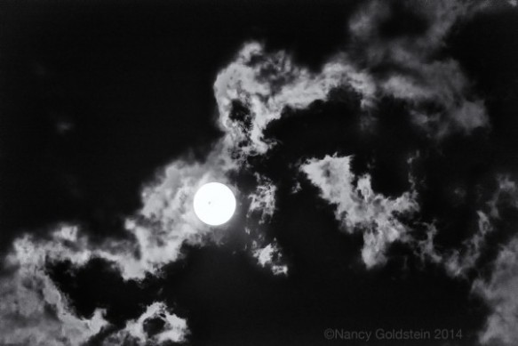 Black and white photo of the full moon on cloudy night